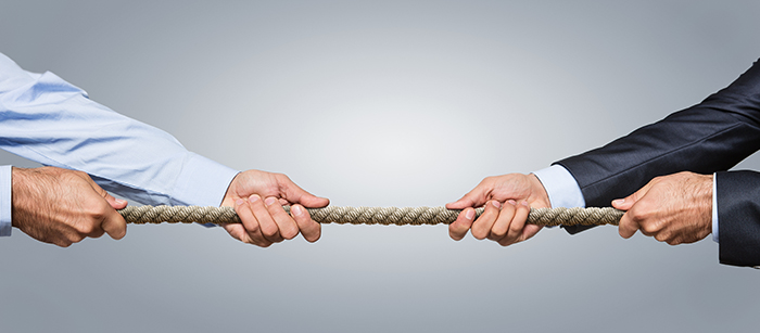 Tug war, two businessman pulling a rope in opposite directions isolated on gray background