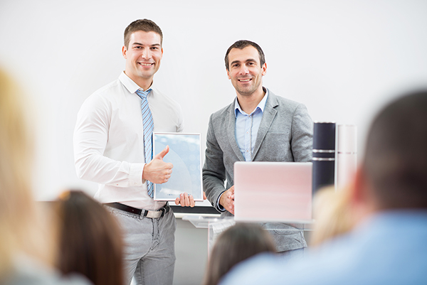 Businessman standing with lecturer while holding certificate and showing thumb up. They are looking at camera.
