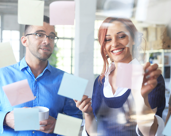 Smiling young people working at the office and taking sticky notes from the glass wall. Man with eyeglasses holding a coffee cup. Tall windows and shelves with boxes on background.